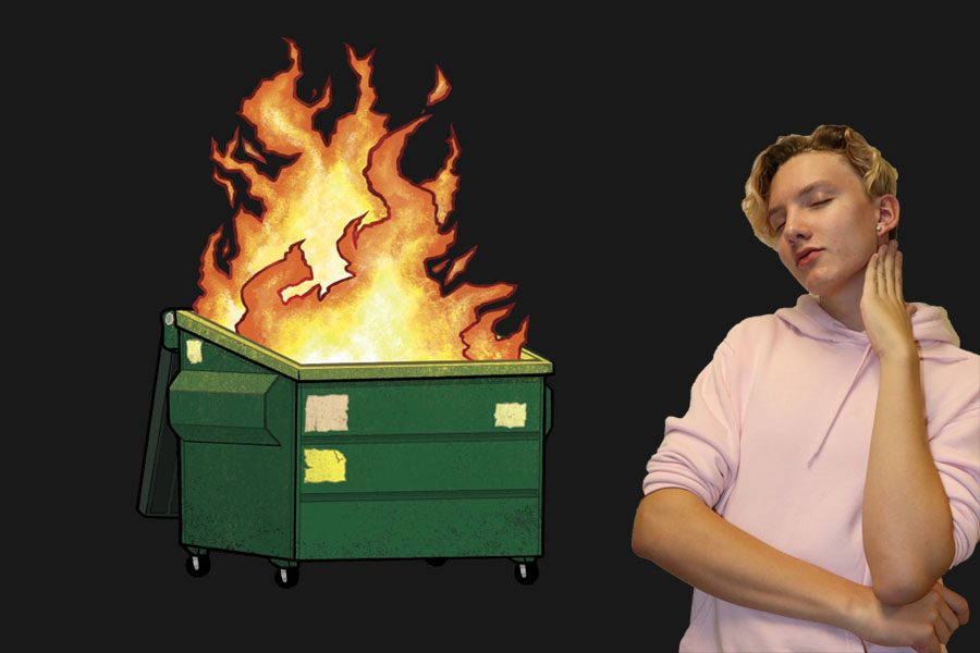 Nick Walfrid is posing next to a burning dumpster.